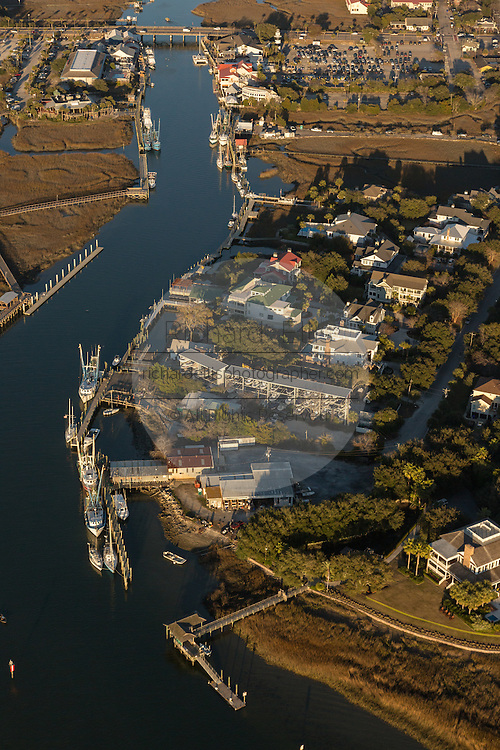 Aerial view of a boat passing through a channel past boat docks in Mt Pleasant, SC