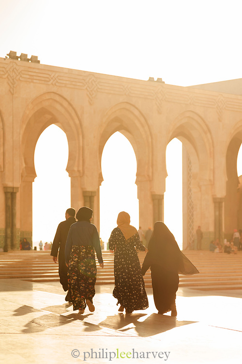 Rear view of people walking towards the archways of Hassan II Mosque, Casablanca, Morocco