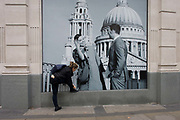 Woman bends down to tie a shoelace beneath a fashion poster showing a fashion couple and St Paul's Cathedral. Stooping down on a ledge at near pavement level, the lady makers her adjustments before continuing her journey. The models are the epitome of youth and happiness, with the backdrop of the capital's famous landmark.