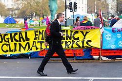 A commuter makes his way past the banners and tents as hundreds of environmental protesters from Extinction Rebellion occupy Marble Arch, camping in the square and even on the streets, blocking access to traffic on Park Lane and Oxford Street in London's usually traffic-heavy west end. . London, April 16 2019.