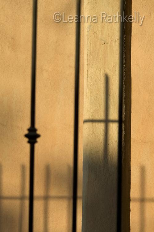 Sayulita, Mexico- a church cross shadow on an earthen-colored adobe building.