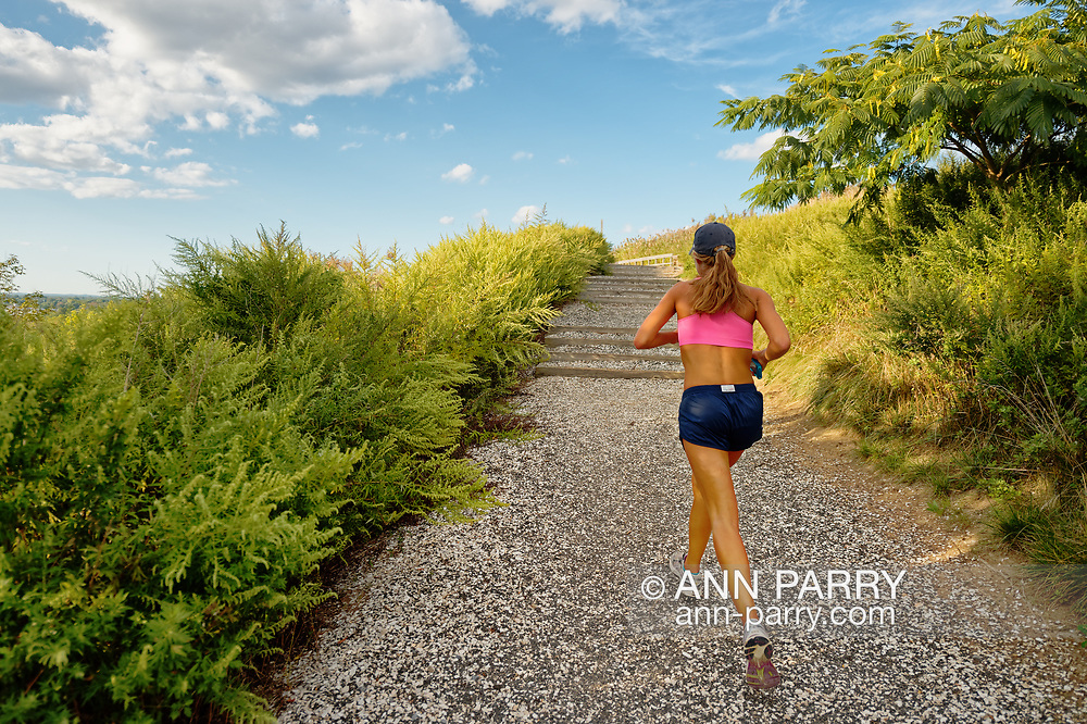 South Merrick, New York, USA. Woman is running uphill on Norman J Levy Park and Preserve Trail, on south shore of Long Island.
