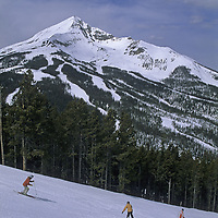 Skiing, Big Sky, Montana. Skiers and a snowboarder descend Ambush run on Andesite Mountain with 11,166 foot Lone Mountain in the background.