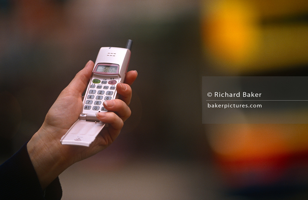 A 1990s flip-up phone handset being used on the street, on 29th March 1996, in Hong Kong, China.