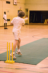 Secondary school students playing indoor cricket in the school sports hall,