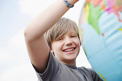 Boy young smiling holding globe balloon