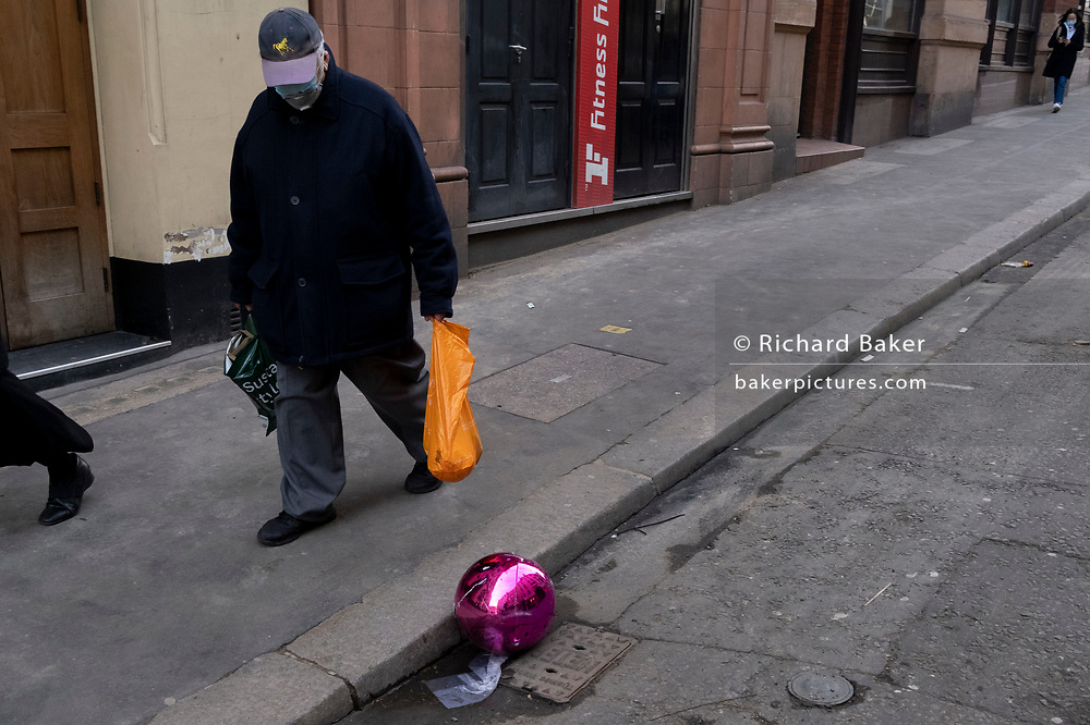 Mask-wearing Londoners walk past a split pink plastic sphere which has come to rest in the gutter on a side street in central London, during the third English lockdown of the Coronavirus pandemic, on 23rd February 2021, in London, England.