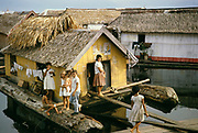 Woman and children in area of Informal housing wooden shacks built on timber logs known as the Floating City, Manaus, Brazil 1962, removed as part of slum clearance policy in late 1960s