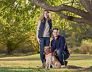 Family photo session at Acton Arboretum. Mom and dad standing under a tree with the family dog.