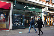 Two women walk past a branch of Clarks, one of the UK's oldest shoe chains, on the second day of England's second coronavirus lockdown on 6 November 2020 in Windsor, United Kingdom. Clarks has been rescued by means of a £100m investment from the Hong Kong-based private equity firm LionRock Capital and will now enter a company voluntary agreement (CVA).
