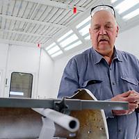 Instructor Floyd Clifford Burnham looks over a newly painted bumper in the paint room of the UNM-Gallup auto body shop Tuesday.