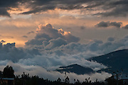 At sunset, clouds creep over Otavalo, Imbabura Province, Ecuador, South America. The culturally vibrant town of Otavalo attracts many tourists to a valley of the Imbabura Province of Ecuador, surrounded by the peaks of Imbabura 4,610m, Cotacachi 4,995m, and Mojanda volcanoes. The indigenous Otavaleños are famous for weaving textiles, usually made of wool, which are sold at the famous Saturday market and smaller markets during the rest of the week. The Plaza del Ponchos and many shops tantalize buyers with a wide array of handicrafts. Nearby villages and towns are also famous for particular crafts: Cotacachi, the center of Ecuador's leather industry, is known for its polished calf skins; and San Antonio specializes in wood carving of statues, picture frames and furniture. Otavaliña women traditionally wear distinctive white embroidered blouses, with flared lace sleeves, and black or dark over skirts, with cream or white under skirts. Long hair is tied back with a 3cm band of woven multi colored material, often matching the band which is wound several times around their waists. They usually have many strings of gold beads around their necks, and matching tightly wound long strings of coral beads around each wrist. Men wear white trousers, and dark blue ponchos. Otavalo is also known for its Inca-influenced traditional music (sometimes known as Andean New Age) and musicians who travel around the world.