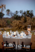 A dinner table is set in the bush at Abu Camp, a luxury safari camp in the Okavango Delta, Botswana