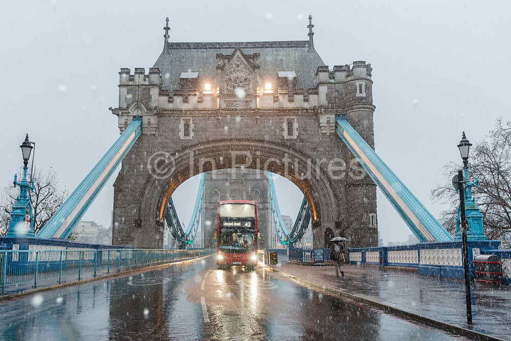 A number 42 double decker bus, destination Liverpool Street, travels across Tower Bridge during a heavy snow shower on December 10th, 2017. Much of the UK has been hit by heavy snow and The Met Office have issued a yellow weather warning for snow and ice across most of the United Kingdom.