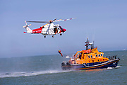 A crew member from HM Coastguard rescue helicopter G-C1JW  attempts to land onto the back of the Royal National Lifeboat Institution RNLI Dover Life boat 17-09 during a training exercise in the sea just outside Folkestone Harbour, Folkestone, Kent. UK. 6th August 2016
