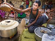 06 NOVEMBER 2014 - SITTWE, RAKHINE, MYANMAR: A Rohingya man cooks snacks he sells in an IDP camp for Rohingya Muslims near Sittwe. After sectarian violence devastated Rohingya communities and left hundreds of Rohingya dead in 2012, the government of Myanmar forced more than 140,000 Rohingya Muslims who used to live in and around Sittwe, Myanmar, into squalid Internal Displaced Persons camps. The government says the Rohingya are not Burmese citizens, that they are illegal immigrants from Bangladesh. The Bangladesh government says the Rohingya are Burmese and the Rohingya insist that they have lived in Burma for generations. The camps are about 20 minutes from Sittwe but the Rohingya who live in the camps are not allowed to leave without government permission. They are not allowed to work outside the camps, they are not allowed to go to Sittwe to use the hospital, go to school or do business. The camps have no electricity. Water is delivered through community wells. There are small schools funded by NOGs in the camps and a few private clinics but medical care is costly and not reliable.   PHOTO BY JACK KURTZ