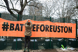 London, UK. 31 January, 2021. An anti-HS2 activist from umbrella campaign group HS2 Rebellion hangs a 'Battle for Euston' banner from fencing erected by HS2 Ltd around Euston Square Gardens. Climbers from the National Eviction Team (NET) are currently dismantling a camp built by activists, five of whom still occupying tunnels beneath the camp, in order to seek to protect trees from felling by HS2 Ltd in connection with the controversial HS2 high-speed rail project.