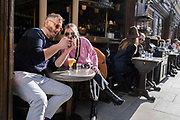 On the day that the UK government eased Covid restrictions to allow non-essential businesses such as shops, pubs, bars, gyms and hairdressers to re-open, customers enjoy outdoor drinks on Old Compton Street in Soho, on 12th April 2021, in London, England.