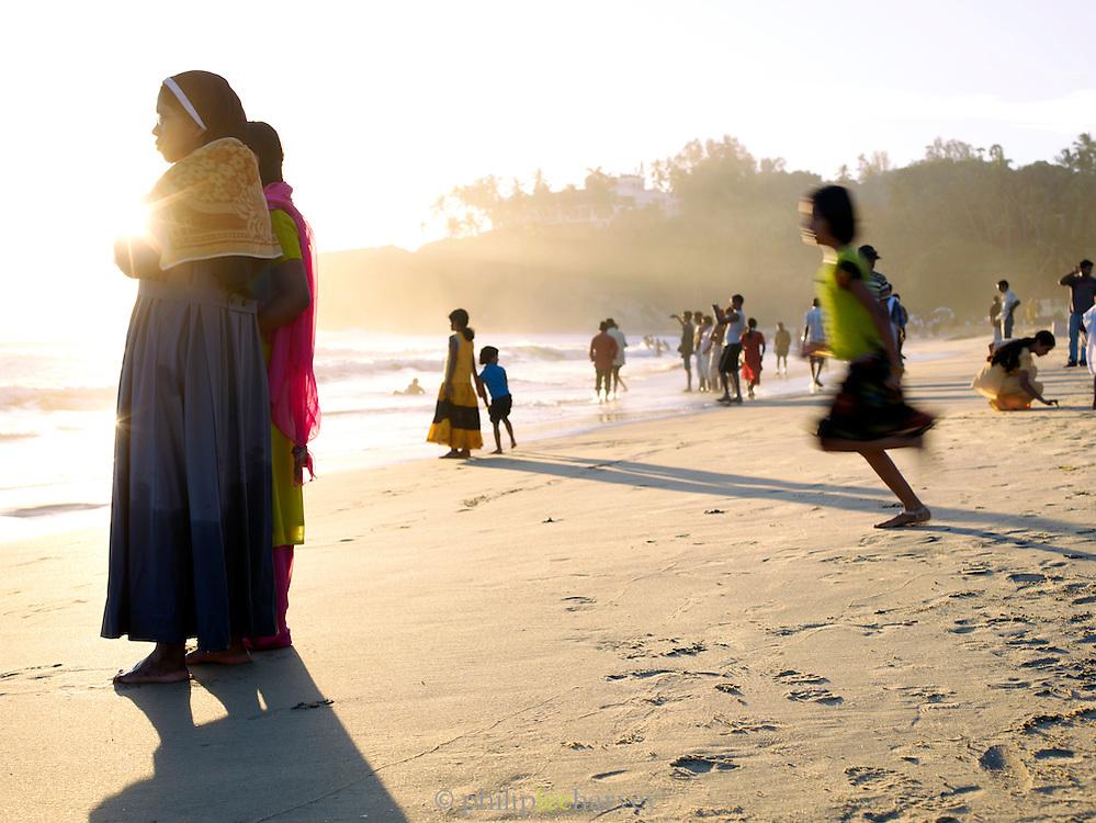 Locals on Papanasham Beach (Beach of Redemption) at sunset, Varkala, Kerala, India