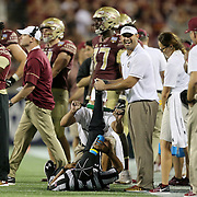 Umpire Michael Cooper drinks and he is treated for a cramp on the field during an NCAA football game between the Ole Miss Rebels and the Florida State Seminoles at Camping World Stadium on September 5, 2016 in Orlando, Florida. (Alex Menendez via AP)