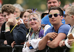 A festival goer watching Kris Kristofferson performing on the Pyramid Stage, at the Glastonbury Festival at Worthy Farm in Pilton, Somerset.