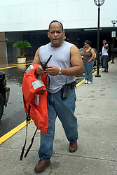 30 August, 2005. Aftermath of Hurricane Katrina, New Orleans, Louisiana. <br /> Police PIO Marlon Defillo tries to get a satellite phone signal outside the Hyatt Hotel downtown.<br /> Photo Credit: Charlie Varley/varleypix.com