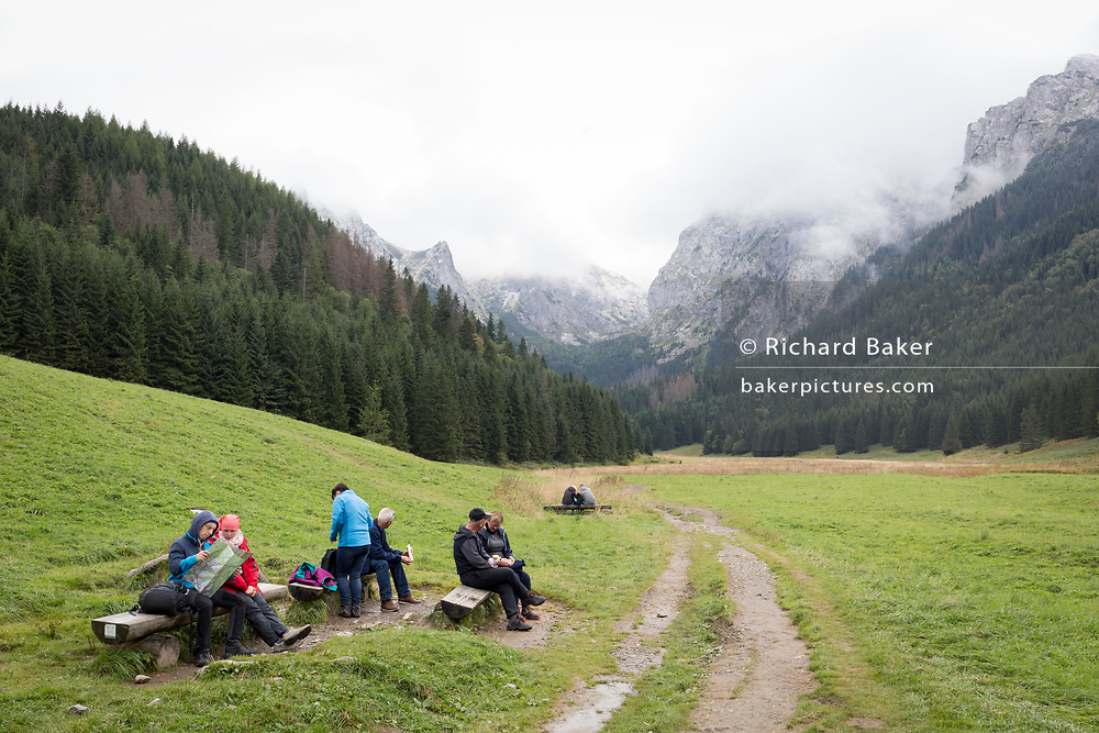 With the mountains of the Tatra National Park and the Slovakian border in the distance, Polish walkers rest on spruce log benches, on 18th September 2019, in Dolina Malejlaki, near Zakopane, Malopolska, Poland.