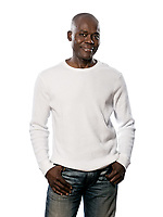 Portrait of a happy casual afro American man standing with hands in pocket in studio on white isolated background