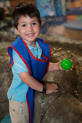United States, Washington, Boy (age 4) playing at water exhibit at KidsQuest Children's Museum.  MR, PR