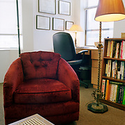 A curved red fabric chair behind a ratan and wood table, on a plain carpet, in front and to the slight left of a black desk chair at a wooden desk, one window in front of the desk and one to the left, a bookcase and ornate metal floor lamp to its left.