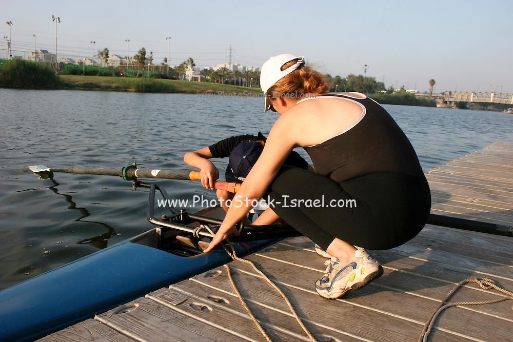 Israel, Tel Aviv, Yarkon River, Rowing training female coach explaining the technique to a teen boy