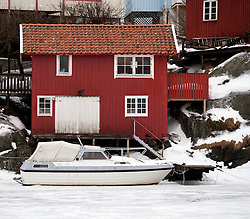 View of red wooden boathouse in traditional harbour and village of Kladesholmen during winter on Bohuslan coast in Sweden