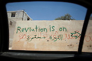 Writing on a wall in the town of Sarmin in Idlib says, 'Revolution is on'. Idlib province in Syria's northwest is one of the few areas in Syria which is currently under FSA control, although this control is patchy and ever shifting. Sarmin, Idlib, Syria.