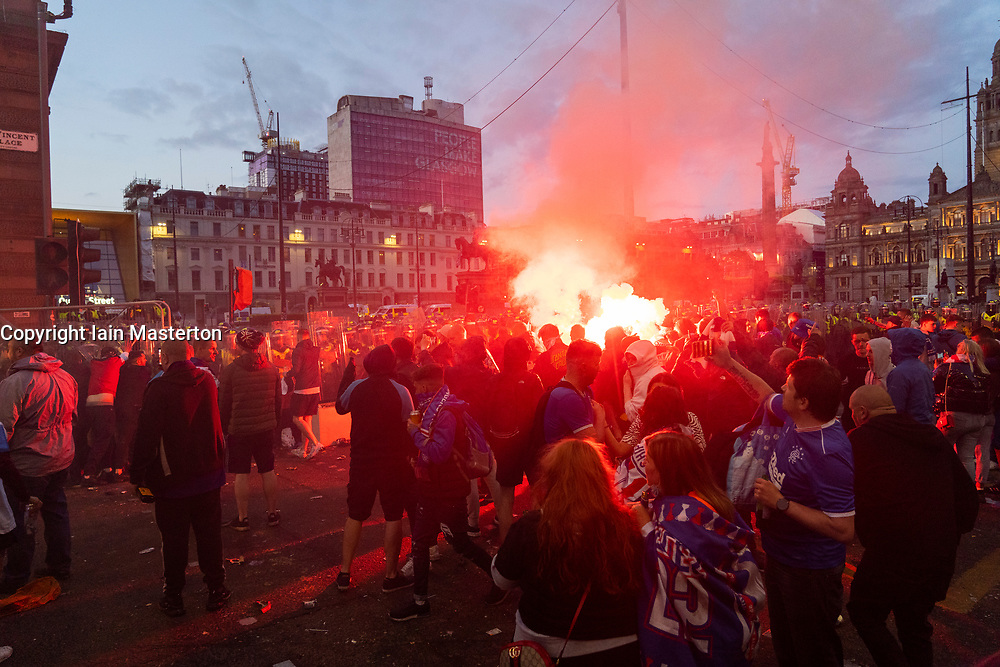 Glasgow, Scotland, UK. 15 May 202. Rangers football supporters  celebrating 55th league victory are cleared from George Square by police in riot gear on Saturday evening. In very violent scenes police were pelted with bottles and items from a nearby construction site as police pushed the supporters into the south west corner of the square. Pic; Violent clashes between police and fans.  Iain Masterton/Alamy Live News.