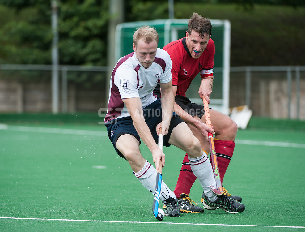 Wimbledon's James Osborn is watched by Dave Wilson of Southgate. Southgate v Wimbledon - Now: Pensions National Hockey League, Premier Division, Trent Park, London, UK on 27 September 2014. Photo: Simon Parker