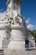 Tourists kiss and hug below the Grade 1 listed Victoria Memorial sculpture opposite Buckingham Palace.