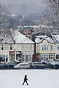 Local resident walks through a snow covered Ruskin Park with background rooftops of residential houses.
