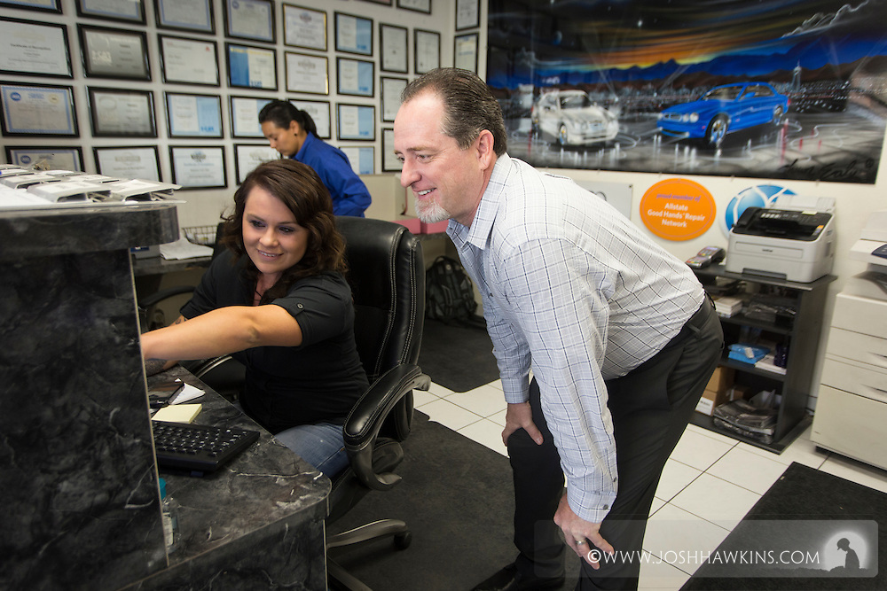 Michael Whittemore, looking at information on a computer screen with front desk employee Emma Vogt<br /> JH_201510021049_MG_5834.CR2<br /> 10/2/2015  --  10:49:18