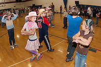 """Caylin Seely (pink) and Bailey Kucckowski """"Do Si Do"""" on the Inter Lakes Elementary School gymnasium/dance floor for the annual Square Dance Thursday afternoon.  (Karen Bobotas/for the Laconia Daily Sun)"""