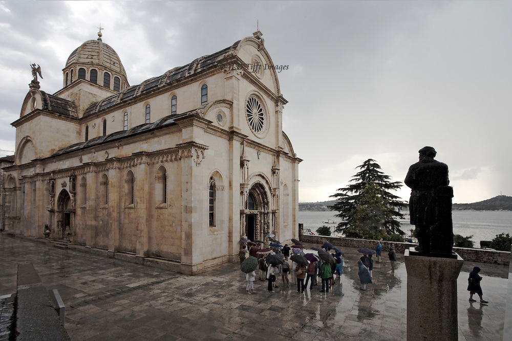 Sibenik, Cathedral of St. James, built 1431-1535.  Architects Juraj (George) of Dalmatia and Niccolo of Florence.  View across the cathedral square in a rainstorm as tourists scurry for cover
