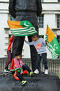 Three boys play on the statue of Field Marshal Montgomery as Kashmiri campaigners protest Indias involvement in Kashmir opposite Downing Street in London, United Kingdom on 13th August 2019. A week ago the Indian Government revoked Article 370, a constitutional provision granting the region special status.