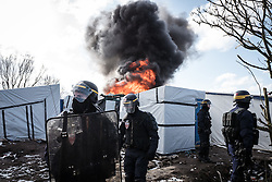 © London News Pictures. Calais, France. 07/03/16. A shelter is set ablaze in the Calais 'Jungle' just behind lines of French riot police. French authorities are evicting and demolishing the southern half of the camp, which charities estimate to contain 3,500 people. . Photo credit: Rob Pinney/LNP