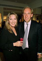 The HON.JAMES & MRS FITZROY-NEWDEGATE he is the son and heir of the 3rd Viscount Daventry, at a party in London on 1st July 1997.LZX 23