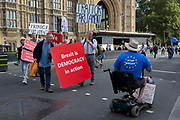 On the day that rebel Conservative Party rebels and opposition MPs attempt to pass a law designed to prevent a no-deal Brexit by the government of Prime Minister Boris Johnson, Brexiteers shout at a disabled pro-EU Remainer outside Parliament, on 3rd September 2019, in Westminster, London, England.