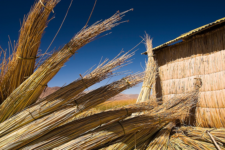 Bundles of dried reeds lay in a pile besides a home on a floating reed island in Lake Titicaca, Peru on August 29, 2005.