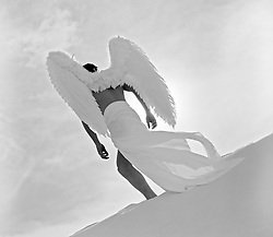 male angel walking on a sand dune in New Mexico