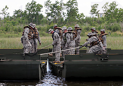 06 May 2010. Shell Beach, Louisiana. Deepwater Horizon, British Petroleum environmental oil spill disaster.<br /> Soldiers from the 2225th Multi-Role Bridge Company Louisiana National Guard commence work on a floating pontoon which will be used by local fishermen to load oil containment boom. With oil reaching ever closer to the St Bernard Parish wetlands, it is vitally important to get more oil containment booms in place.<br /> Photo credit; Charlie Varley/varleypix.com
