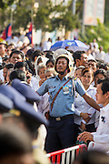 03 FEBRUARY 2013 - PHNOM PENH, CAMBODIA:  A Cambodian police officer tries to hold back the crowd surging to see the crematorium of former King Norodom Sihanouk. Sihanouk ruled Cambodia from independence in 1953 until he was overthrown by a military coup in 1970. The only music being played publicly is classical Khmer music. Sihanouk died in Beijing, China, in October 2012 and will be cremated during a state funeral royal ceremony on Monday, Feb. 4.    PHOTO BY JACK KURTZ