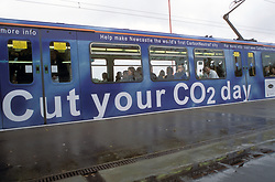 Metro train decorated with Cut Your CO2 Day banner ad; campaign to make Newcastle a carbon neutral city; Newcastle Airport station UK 2011