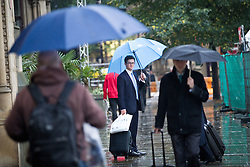 © Licensed to London News Pictures . 02/10/2013 . Manchester , UK . Commuters raise their umbrellas Rain pours in Manchester this morning (2nd October 2013) as the start of October signals the end of Summer . Photo credit : Joel Goodman/LNP